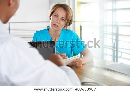 Team of doctor and nurse discussing a patient diagnosis sitting at the desk in bright modern office - stock photo