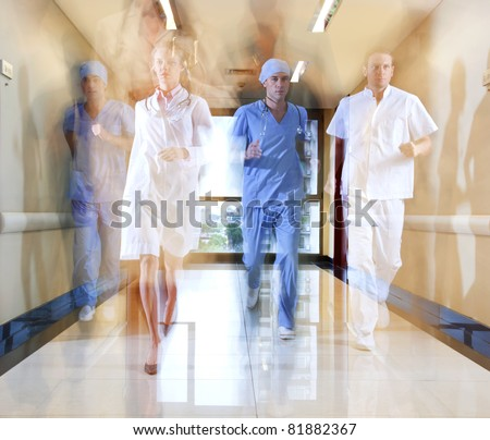 Team of doctor and nurse running in hallway of hospital - stock photo