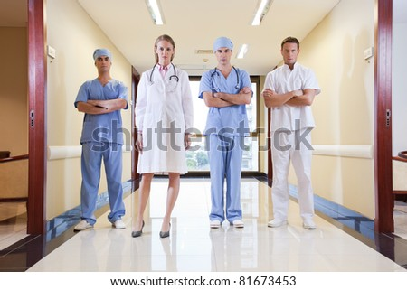 Team of doctor and nurse standing in hallway of hospital - stock photo