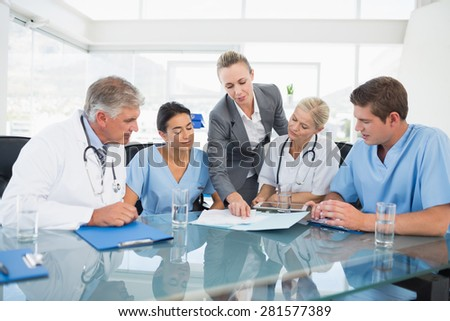 Team of doctors and businesswoman having a meeting in medical office - stock photo
