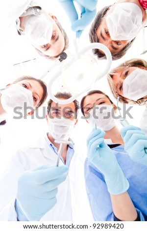 Team of doctors holding medical instruments at the hospital - stock photo