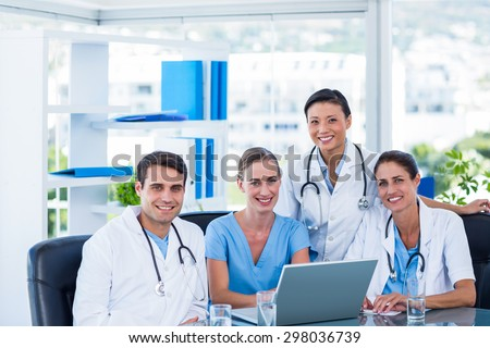Team of doctors smiling at camera in the meeting room - stock photo