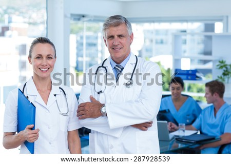 Team of doctors standing arms crossed and smiling at camera in medical office - stock photo