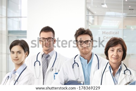 Team of doctors standing in hospital lobby, looking at camera, smiling. - stock photo