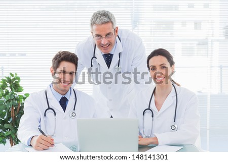 Team of doctors working together with their laptop looking at camera in medical office - stock photo