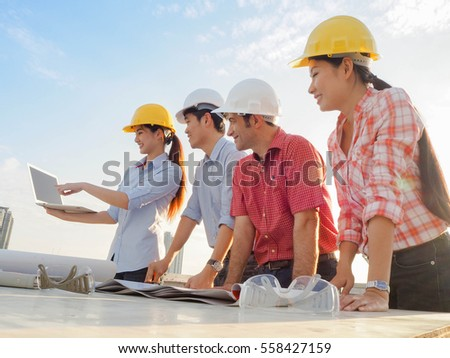 Team of engineers and technician meeting on top of building site