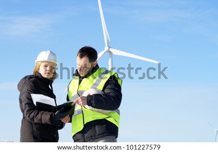 team of  engineers or architects with white safety hat and wind turbines on background - stock photo