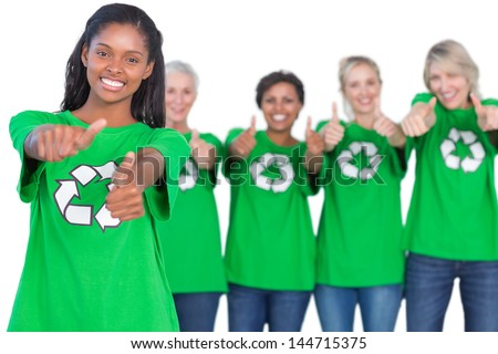 Team of female environmental activists smiling at camera and giving thumbs up on white background - stock photo