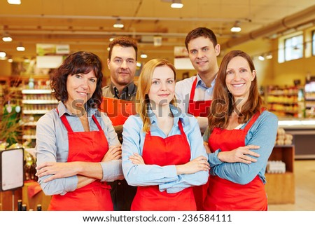 Team of five happy salespeople together in a supermarket with their arms crossed - stock photo