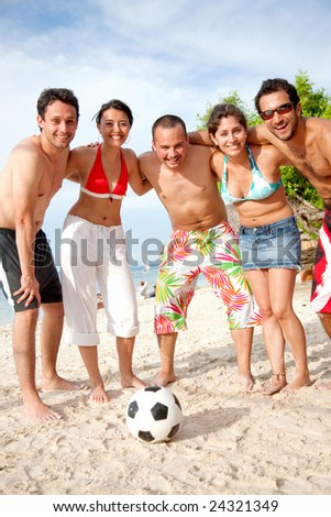 Team of football players standing at the beach with a ball - stock photo