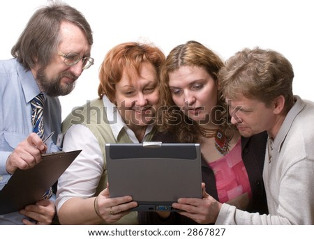 team of four business people looking with great interest at screen of notebook on white background