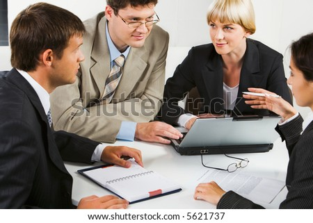 Team of four business people sitting at the table with laptop, notepad, papers, glasses on it and discussing an important question