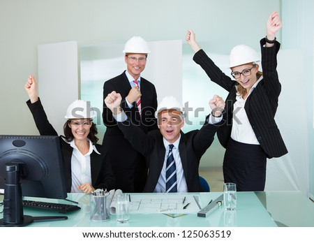 Team of four diverse architects or structural engineers wearing hardhats in an office cheering and raising their hands in the air - stock photo