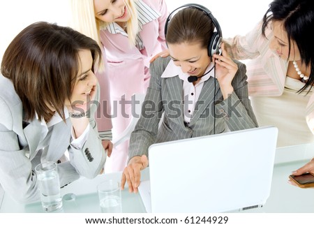 Team of four successful businesswoman laughing behind laptop, one with headset