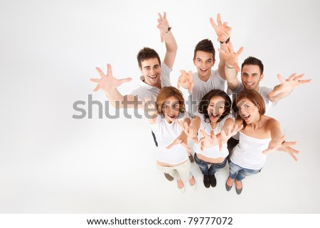 team of friends looking above, reaching for the camera - stock photo