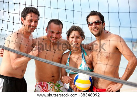 Team of friends playing volleyball at the beach - stock photo