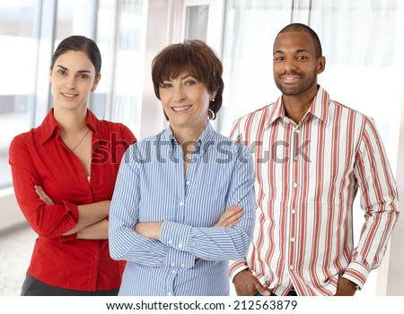 Team of happy caucasian business people standing in office looking at camera smiling, standing, arms crossed. - stock photo