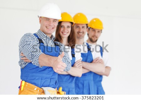 Team of happy workers in uniform ready to work - stock photo