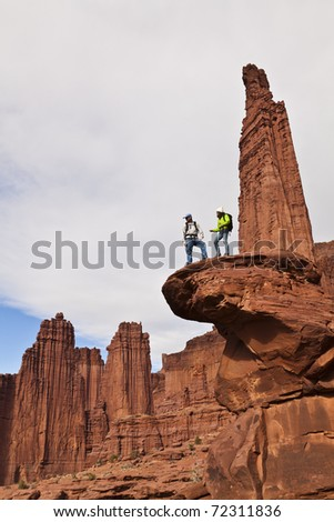 Team of hikers on the summit of a sandstone spire in Canyonlands National Park.