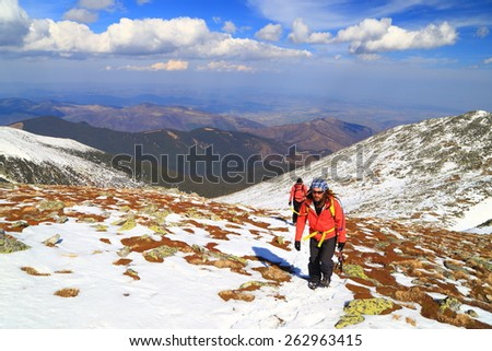 Team of hikers walking on snow covered mountain slope in sunny day of winter - stock photo