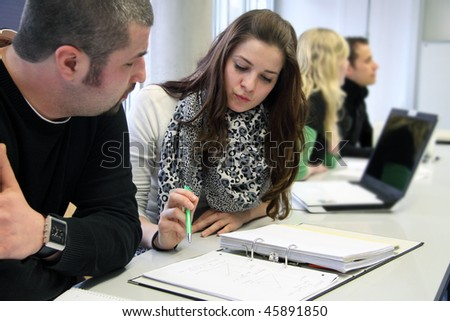 Team of international young students discussing lesson topics in a group