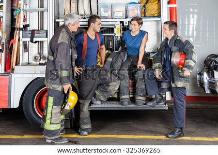 Team of male and female firefighters conversing by firetruck at station - stock photo