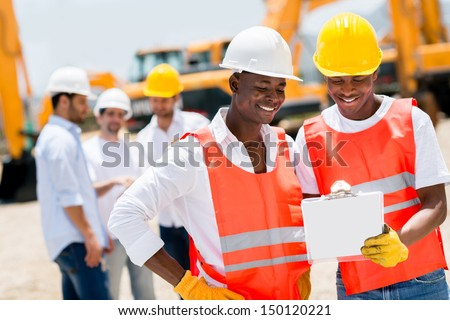 Team of male workers at a building site looking happy  - stock photo