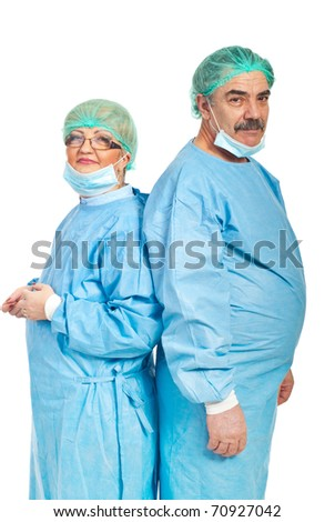 Team of mature surgeons standing back to back and looking camera isolated on white background - stock photo