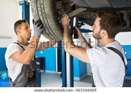 Team of mechanics repair wheel on the car at workstation