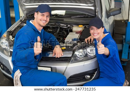 Team of mechanics smiling at camera at the repair garage - stock photo