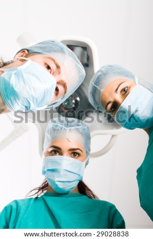Team of medical doctors looking down at patient in surgical theater - stock photo