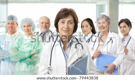 Team of medical professionals lead by senior female doctor looking at camera, smiling. - stock photo