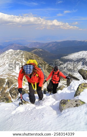Team of mountaineers during the ascent of snow covered route in fine winter day - stock photo