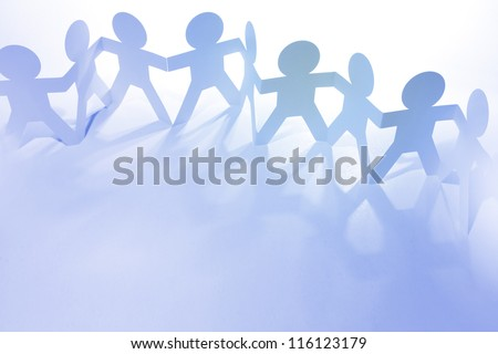 Team of paper chain people holding hands - stock photo