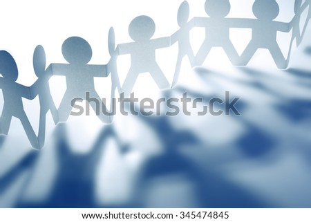 Team of paper doll people casting shadows. Blue tone. - stock photo