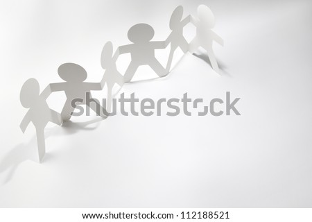 Team of paper doll people holding hands. Teamwork concept - stock photo