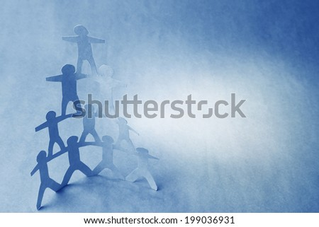 Team of paper doll people, human pyramid - stock photo