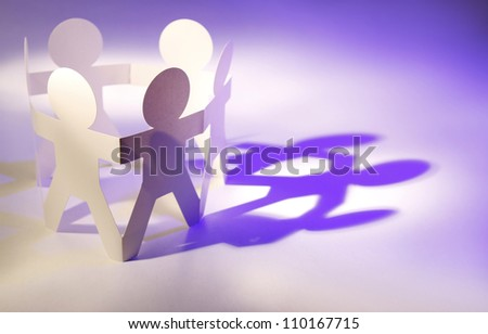 Team of paper doll people in a circle - stock photo