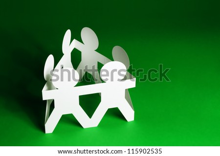 Team of Paper Dolls holding Hands on Green Background - stock photo