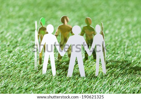 Team of paper people standing in circle on grassy field - stock photo