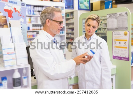 Team of pharmacists speaking about medication in the pharmacy - stock photo