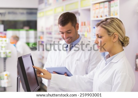 Team of pharmacists using computer at the hospital pharmacy - stock photo