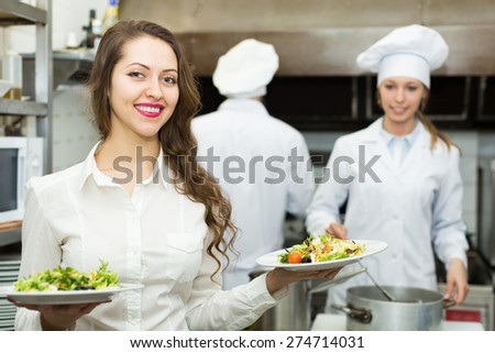 Team of positive chefs and young waiter in restaurant kitchen  - stock photo