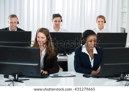 Team Of Professional Businesspeople Working On Computers In Call Center - stock photo