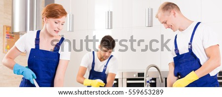 Team of professional cleaners cleaning a modern kitchen