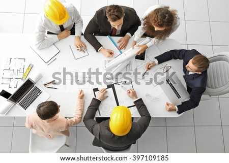 Team of professional engineers working with blueprints - stock photo