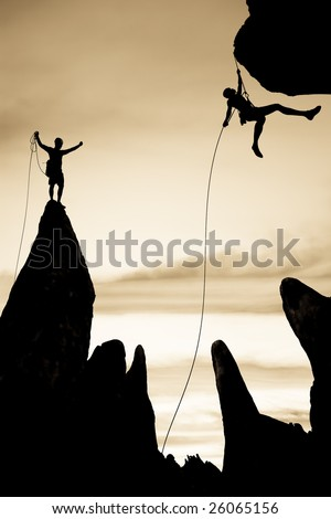 Team of rock climbers silhouetted on the summit,  dangle in midair rappelling from a rock spire in The Sierra Nevada Mountains. - stock photo