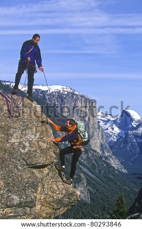 Team of rock climbers struggle to reach the summit of a steep pinnacle. - stock photo