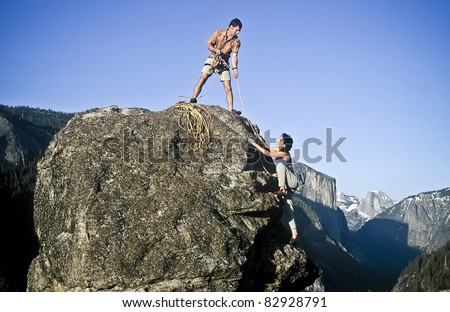 Team of rock climbers struggle to reach the summit of a steep pinnacle.