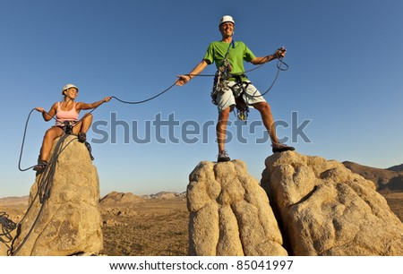 Team of rock climbers struggle to the summit of a challenging cliff. - stock photo